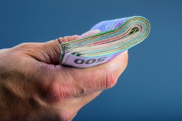 彼の指でお金の束を保持している成熟した男。ユーロ通貨紙幣。