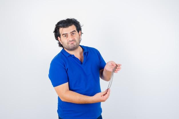 성숙한 남자 체인을 잡고, 파란색 티셔츠에 입술을 커브 하 고 의아해, 전면보기를 찾고.