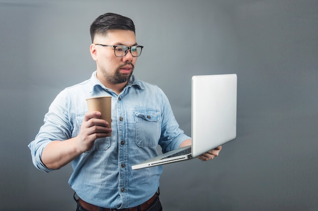 A mature man holding a computer and coffee