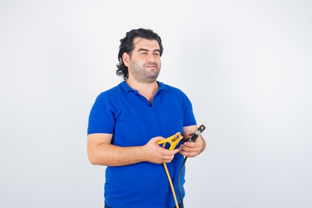 Зрелый мужчина держит строительные инструменты в синей футболке и выглядит вдумчиво. передний план.