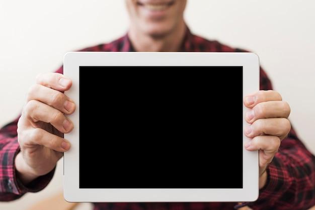 Mature man holding an empty tablet