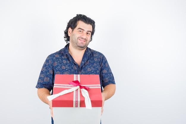 성숙한 남자 셔츠에 선물 상자를 들고 귀여운, 전면보기를 찾고.