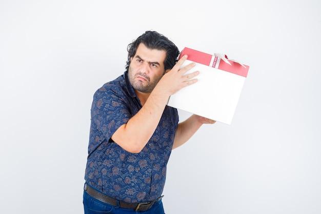 Зрелый мужчина держит подарочную коробку возле уха в рубашке и смотрит любопытно, вид спереди.