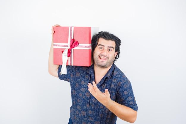 셔츠에 제스처를 심문 하 고 쾌활 한, 전면보기에 손을 스트레칭하는 동안 어깨에 선물 상자를 들고 성숙한 남자.