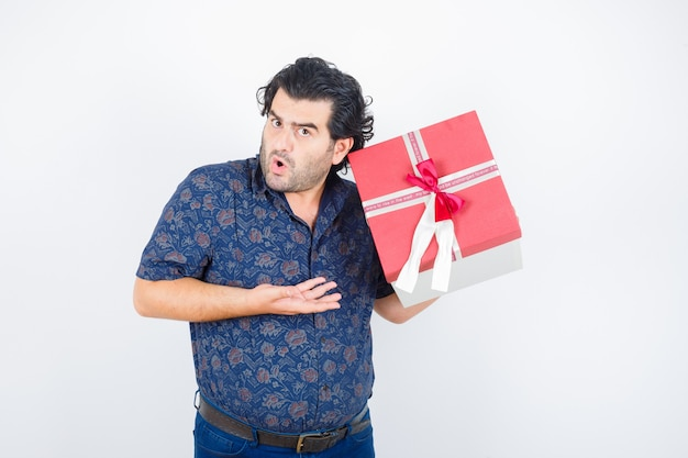 Mature man holding gift box while presenting in shirt and looking puzzled , front view.