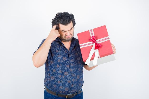 셔츠에 머리를 긁적 하 고 사려 깊은 찾고있는 동안 선물 상자를 들고 성숙한 남자. 전면보기.