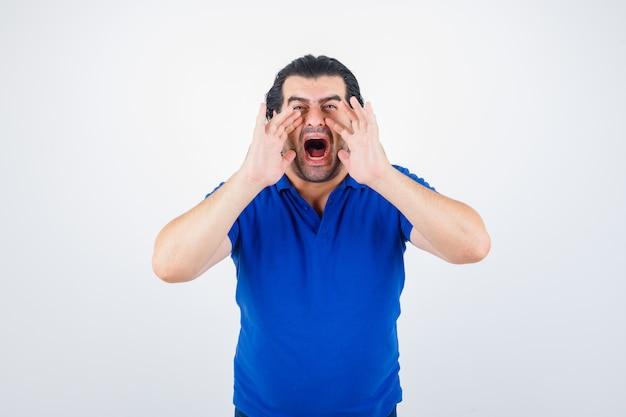 Uomo maturo che si tiene per mano vicino alla bocca come chiamare qualcuno in maglietta blu