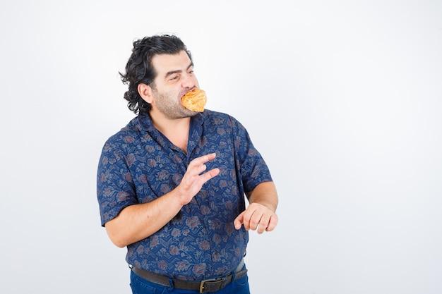 Uomo maturo che tiene il prodotto di pasticceria sulla bocca mentre distoglie lo sguardo in camicia e sembra felice, vista frontale.
