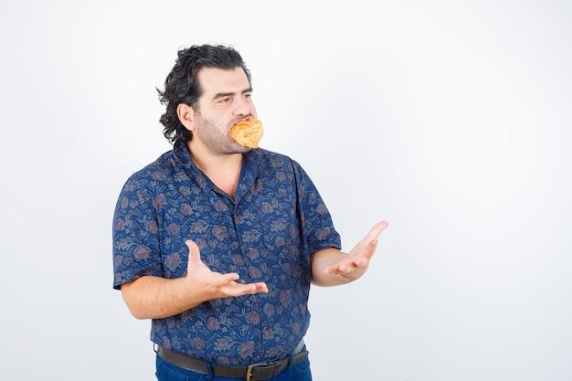 シャツに積極的に手を保ち、真面目な正面図でペストリー製品を口に持つ成熟した男。