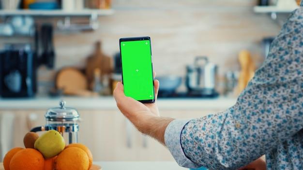 부엌에서 아침 식사를 하는 동안 녹색 화면이 있는 스마트폰을 들고 있는 성숙한 남자. 쉽게 교체할 수 있도록 크로마 키 격리 모형 모형이 있는 노인