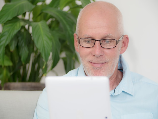 Mature man at home websurfing on internet