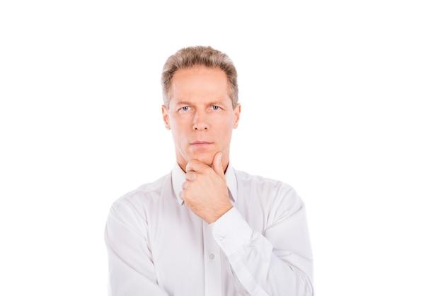 Зрелый мужчина в рубашке с рукой на подбородке