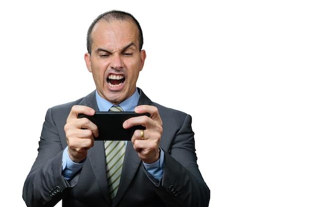 성숙한 남자 양복과 넥타이, 자신의 스마트 폰에서 재생 및 화난 얼굴.