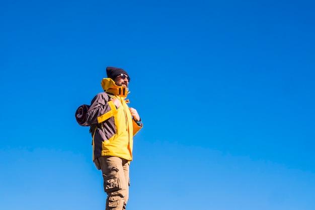 青い空を背景にバックパックとサングラスの成熟した男。青い空を背景に何か面白いものを賞賛するニット帽、サングラス、バックパック、イエロージャケットの男性ハイカー