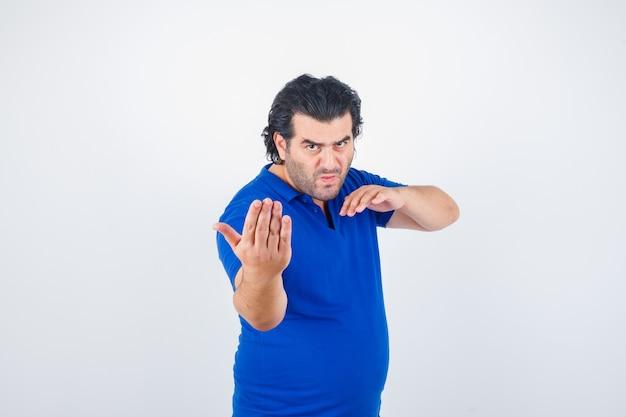 Зрелый мужчина в синей футболке, джинсах стоит в боевой позе и выглядит сосредоточенным