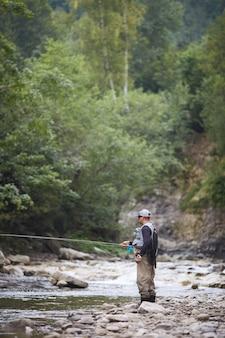 모자와 야외에서 물고기를 잡기 위해 막대를 사용하여 제복을 입은 성숙한 남자. 빠른 강에서 여름 낚시. 주변 산 녹색 자연.