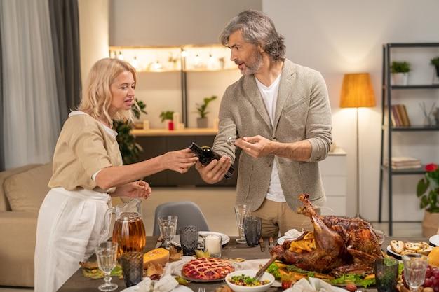 Зрелый мужчина в повседневной одежде показывает жене бутылку красного вина, собираясь поставить ее на праздничный стол с домашней едой