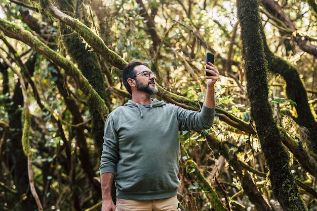 森の中で携帯電話を使用してselfieまたはビデオチャットをしている眼鏡の成熟した男。自然の中でスマートフォンで信号を探している男性の観光客。森の中で電話を使ってネットワークを探している男。