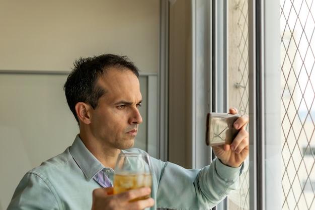 Зрелый мужчина перед окном принимает виски и смотрит видео на своем смартфоне.