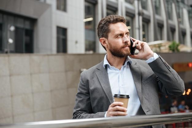 ビジネスコール中にモダンなビジネスセンターの前でテイクアウトコーヒーを立って保持しながら、よそ見灰色のスーツを着た中年の男性