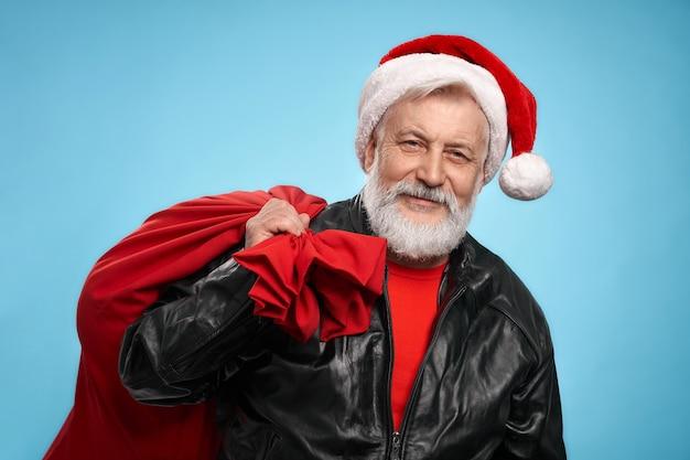 Зрелый мужчина в новогодней шапке и кожаной куртке с красным мешком
