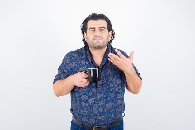お茶の匂いを嗅ぎながらカップを持って喜んでいるシャツを着た成熟した男、正面図。