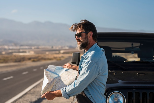 선글라스를 쓴 성숙한 남자가 고속도로에서 지프 보닛 옆에 서 있는 동안 위치 지도에서 방향을 찾고 있습니다. 지도를 읽고 차 옆을 바라보는 잘생긴 남자