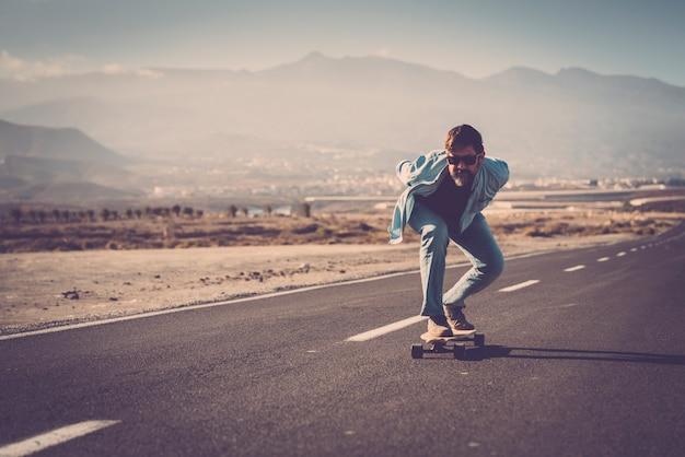 山を背景に田舎道で彼のロングボードに乗って手を後ろにサングラスをかけた成熟した男。山道でスケートやロングボードをする男性