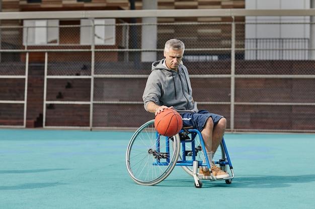 屋外のスポーツグラウンドでバスケットボールをする車椅子の成熟した男