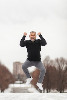Mature man jumping of happiness