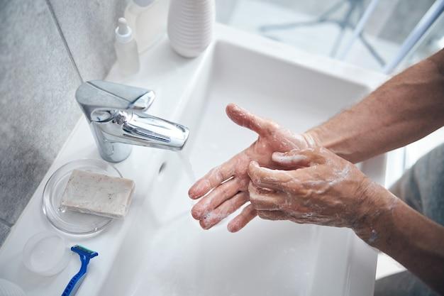 싱크대 위에 비누로 자신의 손바닥을 비누 칠하는 성숙한 남자