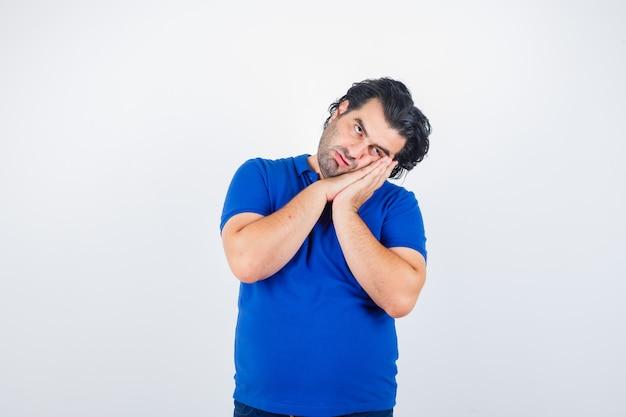 Uomo maturo che si appoggia sulle palme come cuscino in maglietta blu e che sembra pensieroso. vista frontale.