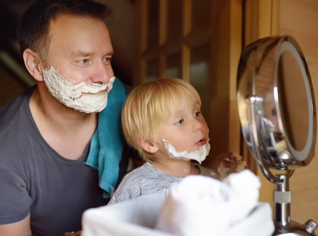 Mature man and little boy having fun with foam during shaving together. kid son imitates his father.