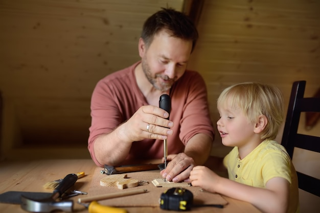 Mature man and little boy make a wooden toy together.