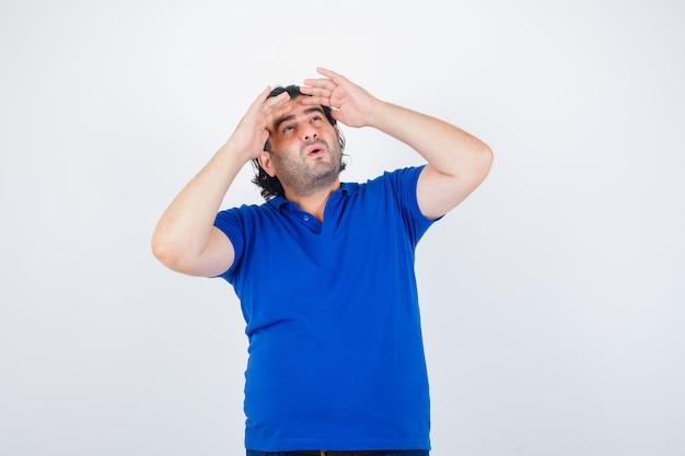 Uomo maturo che guarda lontano con la mano sopra la testa in maglietta blu, jeans e guardando sorpreso, vista frontale.