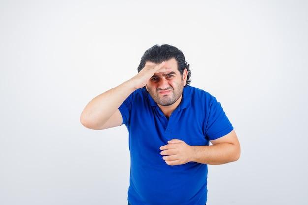 青いtシャツ、ジーンズを着て頭上に手を渡して遠くを見て、集中して見える成熟した男。正面図。