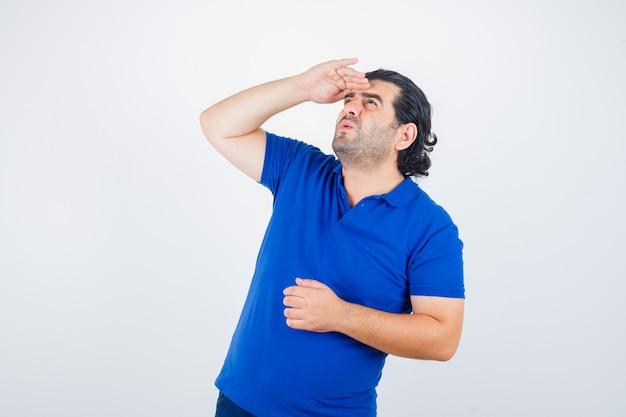 Зрелый мужчина смотрит вдаль с рукой над головой в синей футболке, джинсах и выглядит сосредоточенным. передний план.