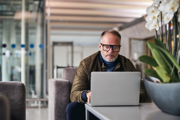 Зрелый мужчина пристально смотрит на свой ноутбук