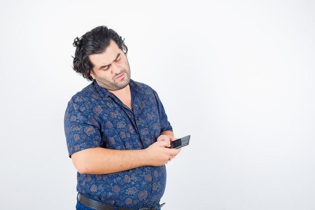 Uomo maturo guardando il telefono cellulare in camicia e guardando pensieroso, vista frontale.