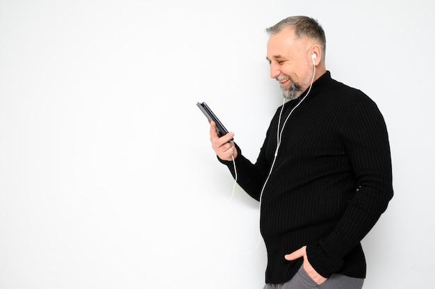 Зрелый человек смотрит на свой телефон с копией пространства