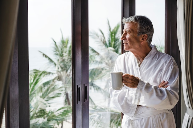 Mature man looking out the hotel window