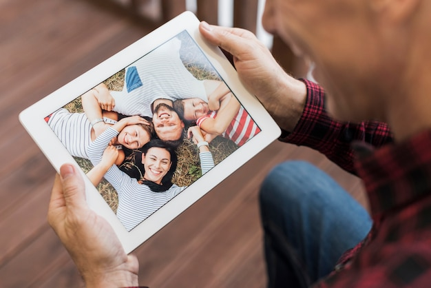 Mature man looking on photos with his children and grandchildren