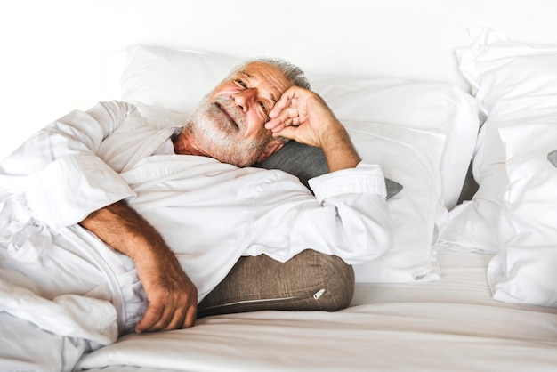 Mature man lying on a bed