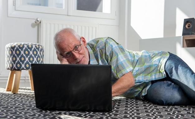 床に横になってラップトップを使用して成熟した男