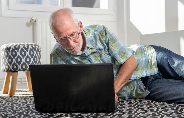 Зрелый мужчина лежал на полу и использовал ноутбук