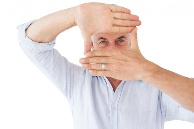 Зрелые мужчина делает кадр с руками