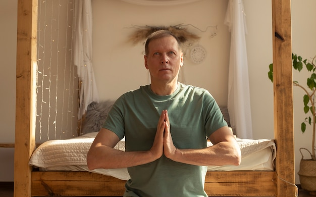 Зрелый мужчина медитирует в уютном доме, держа руки вместе в позе медитации