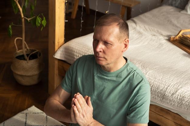 Зрелый мужчина медитирует в уютном доме, держа руки вместе