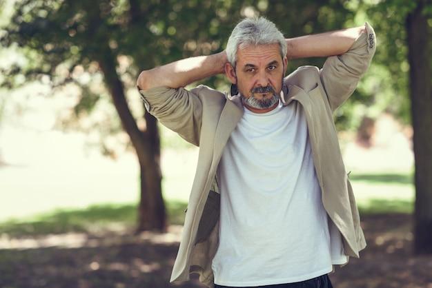 Mature man, model of fashion, in an urban park.