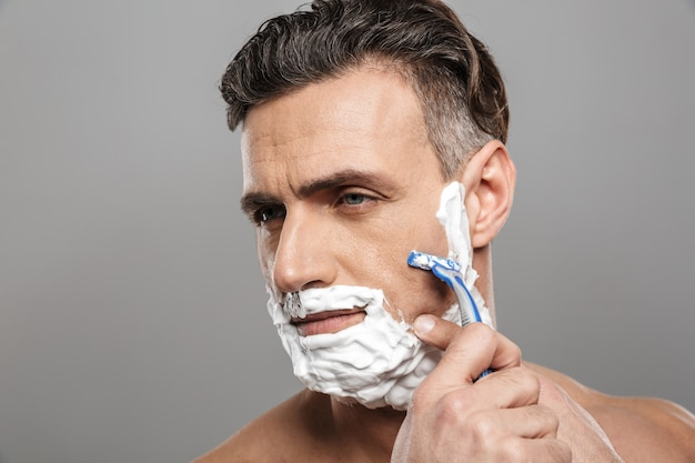Mature man naked shaving.
